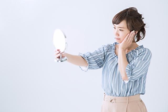 鏡をみて、肌のハリを気にする女性