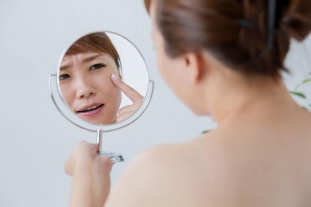肌トラブルに悩み鏡を見る