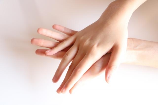 両手を重ねる女性